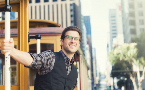 man outside of trolley smiling with glasses