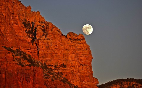 moon gleaming behind a red rock mountain