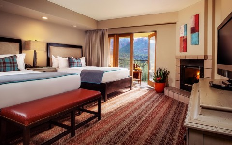 guest room with two white linen beds, patterned red carpet, balcony, fireplace, and desk area