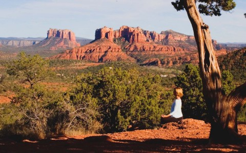 woman doing yoga on a trail overlooking the red rock mountains