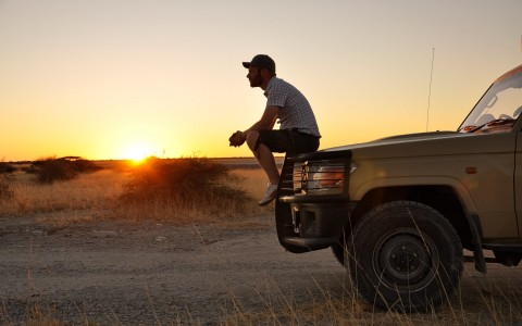 a man sitting on the hood of a car on the side of a desert road with the sun going down in the distance