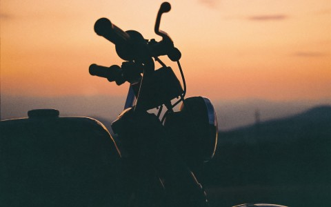 dark image of a motorcycle with the sunset in the background
