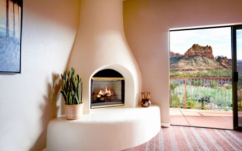 in room stone fireplace next to an open balcony door