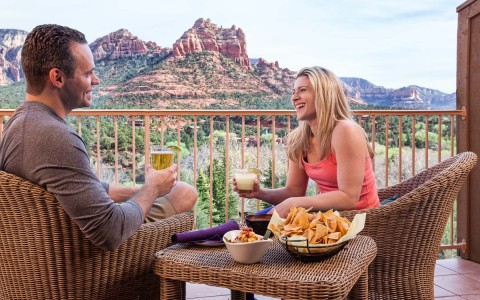 man and woman sitting on a balcony having drinks and appetizers enjoying the red rocks views