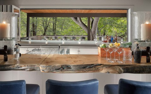 bar area with wood countertops and a view of trees outside behind the bar