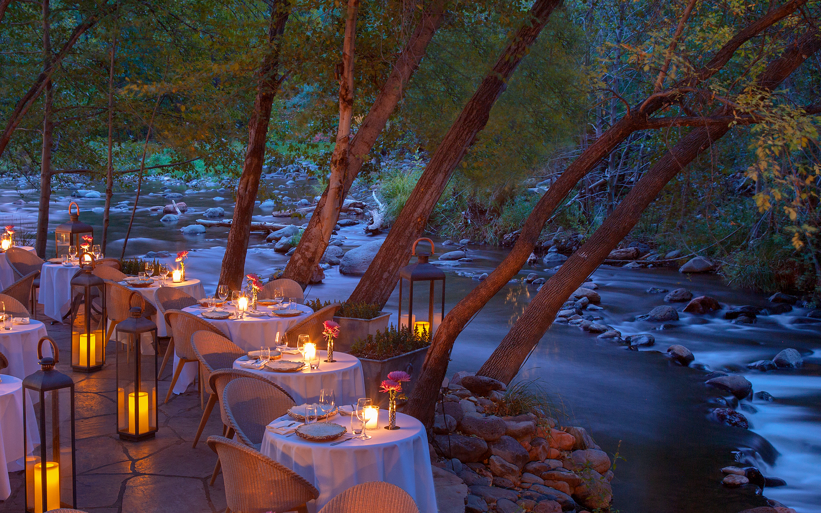 outdoor restaurant dining area with candle lit tables by a creek