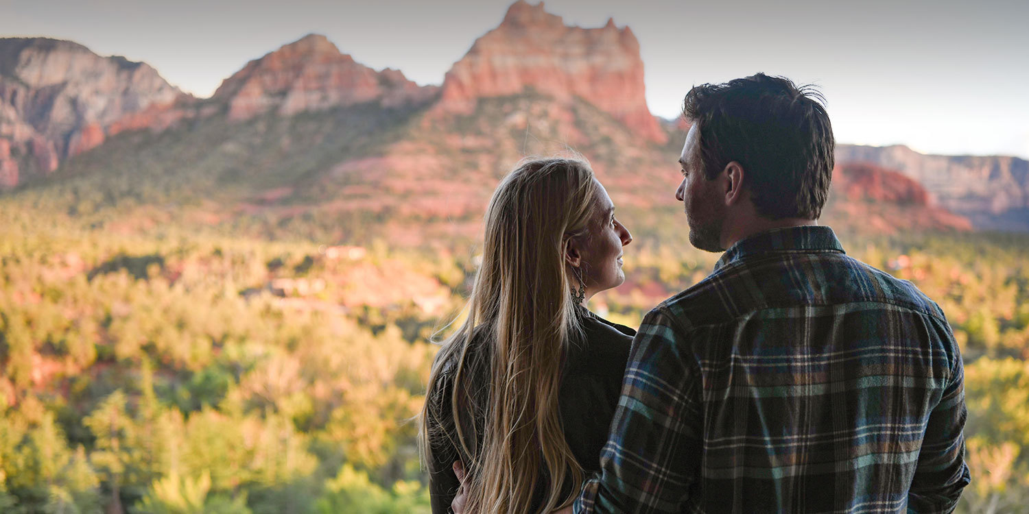 couple on balcony looking at red rock mountains view