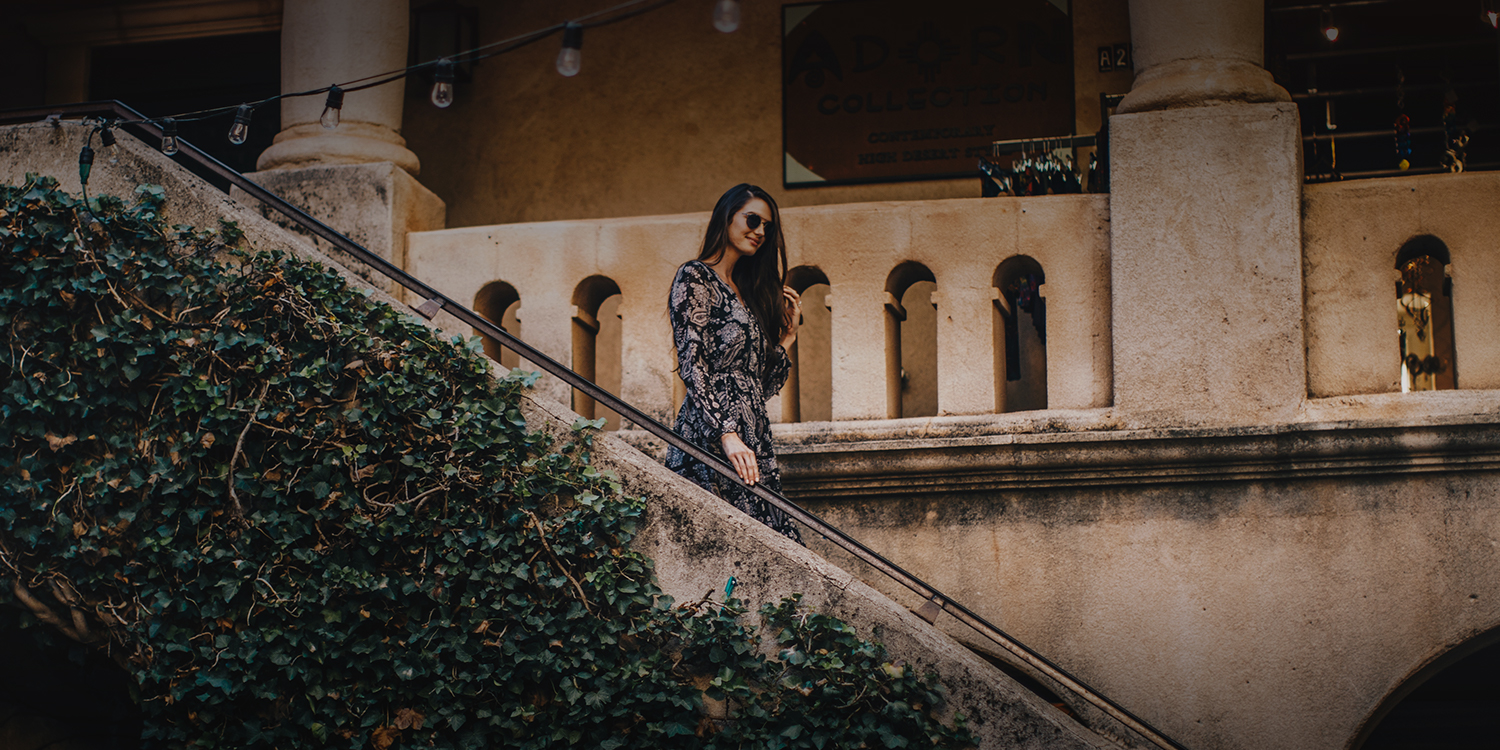 well dressed woman walking down a set of stairs next a stone building