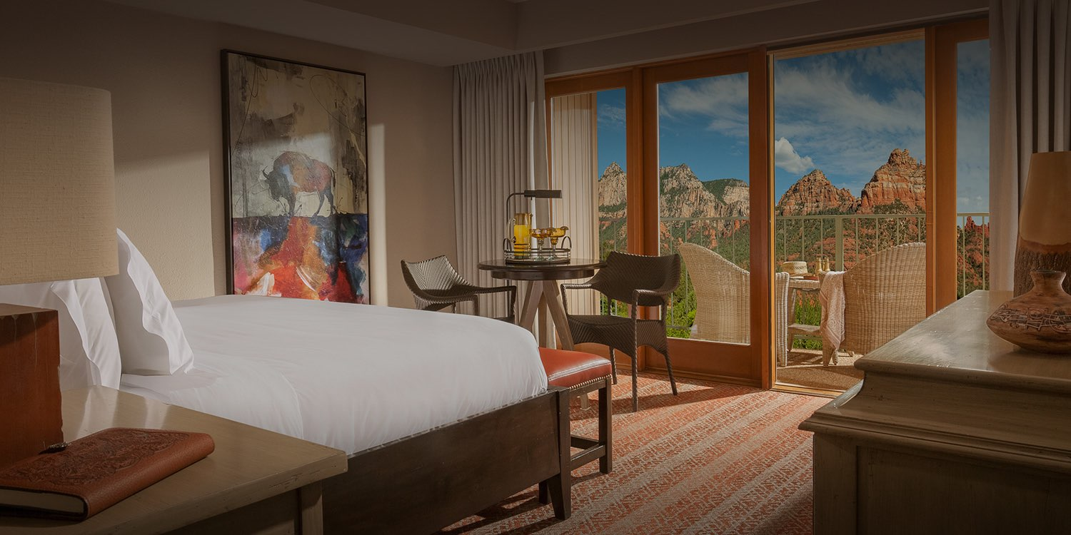 guest room with a bed facing glass doors with a view of the red rock mountains