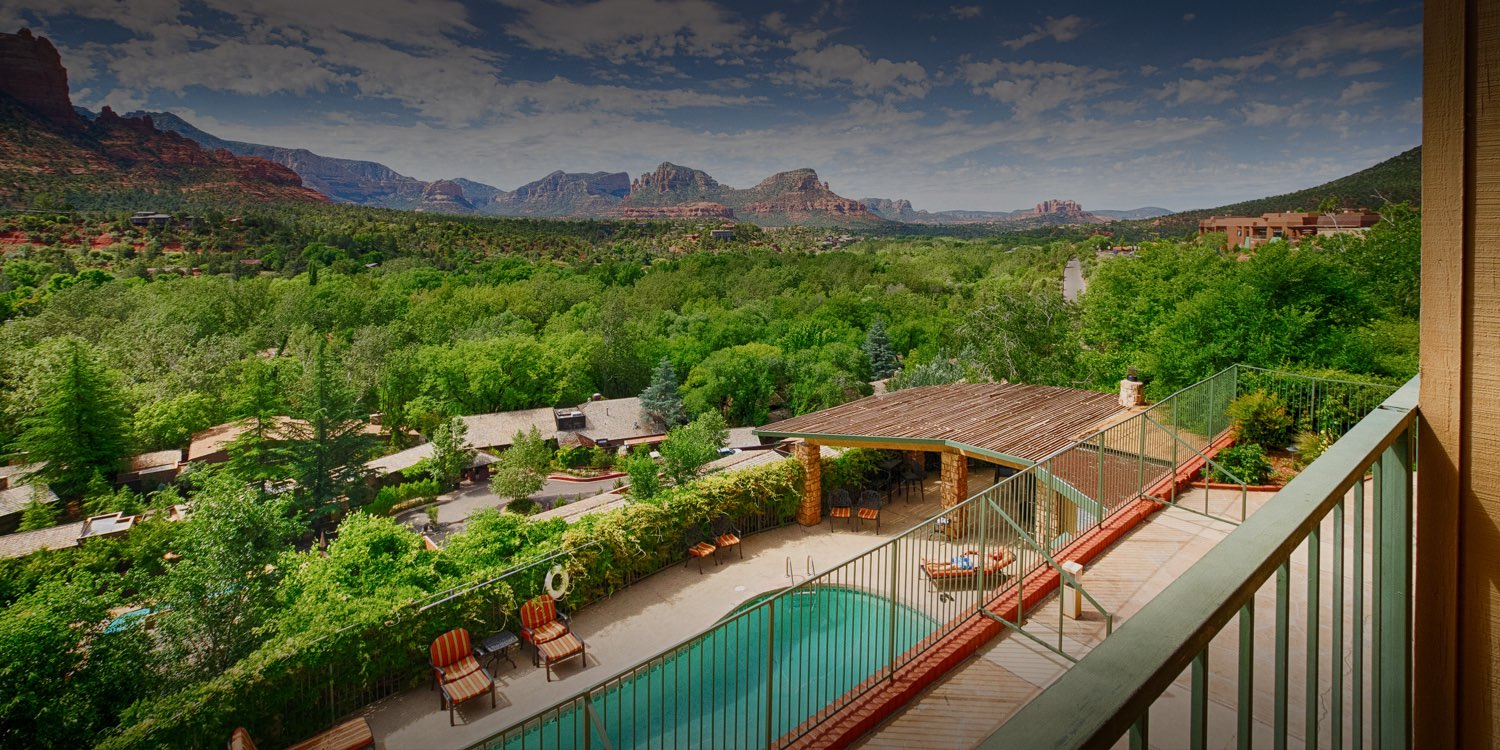 view of the pool area from a guest balcony overlooking the mountains in the distance