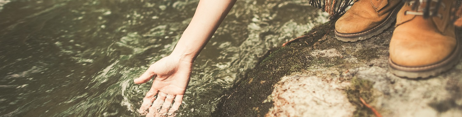 close up of a person dipping their hand in creek water