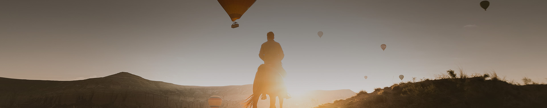 man riding a horse with the sun gleaming in the distance and hot air balloons in the sky