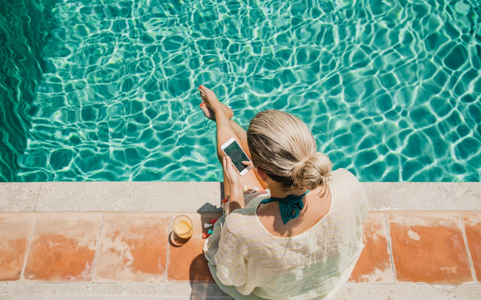 overhead view of a woman sitting by the edge of the pool on her phone