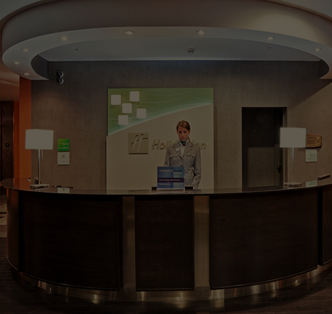 Woman standing behind the front desk at a Holiday Inn hotel