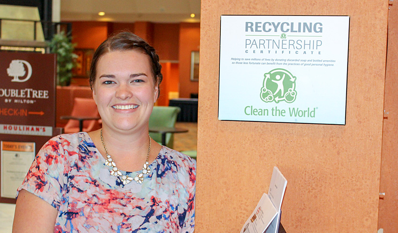 Woman smiling next to a recycling poster