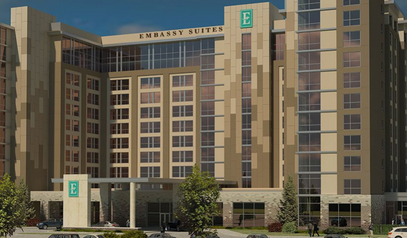 Rendering of the exterior of an Embassy Suites hotel and parking lot in Denton, TX