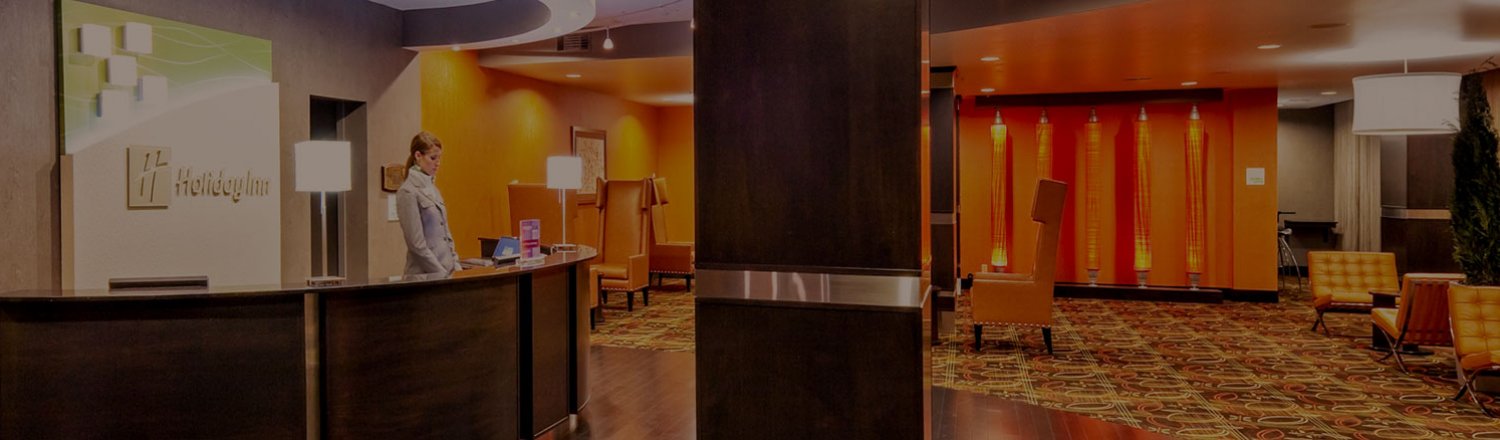 Interior of Holiday Inn lobby with woman at front desk