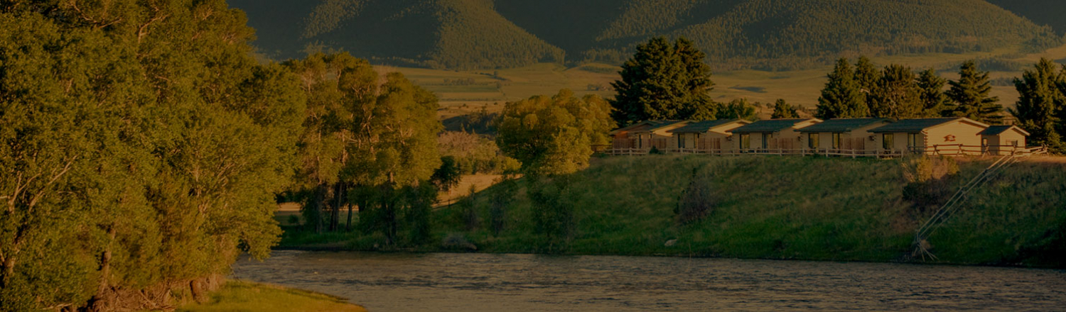 Yellowstone Valley Lodge cabins on a hill behind a river
