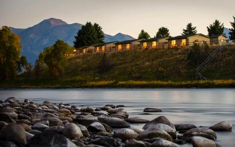 Yellowstone Valley Lodge cabins on a hill behind a river with mountains in the background