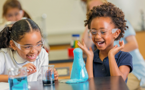 Two young girls laughing as they conduct a science experiment