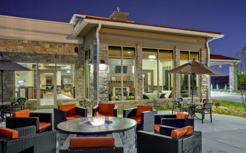 Hotel exterior patio area with fire pit surrounded by eight cushioned chairs