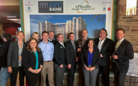 Team members posing in front of Embassy Suites poster