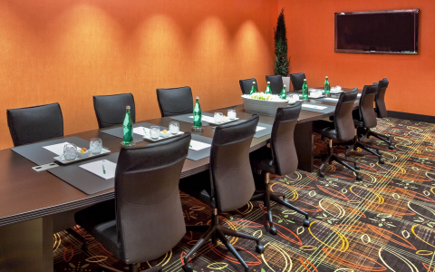 Conference room with a long table surrounded by 12 chairs and a flat screen TV mounted on the wall