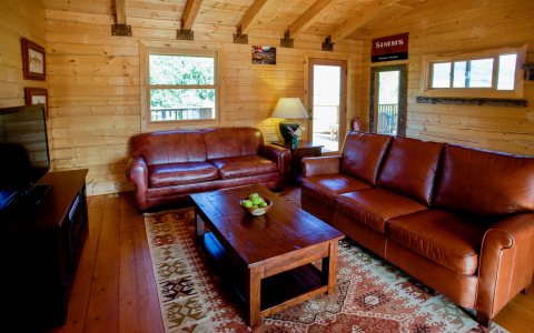 Log cabin interior with a leather couch and love seat, wooden table and entertainment center with a flatscreen TV