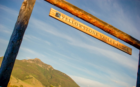 Yellowstone Valley Lodge sign on wooden posts with a mountain in the background