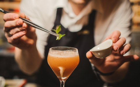 bartender topping of a drink with small garnish