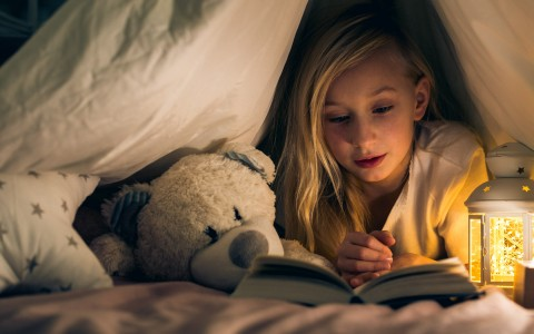 little girl reading in a tent with her teddy bear