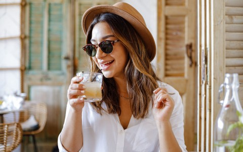 woman with cool hat sipping a cocktail