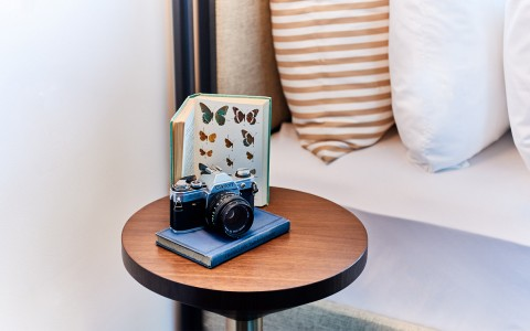 wooden side table with an old film camera