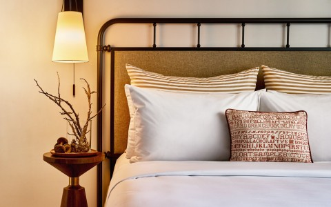 hotel bed with white and beige pillows