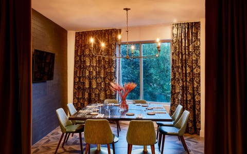 large dining table in front of large sliding window with big classic curtains