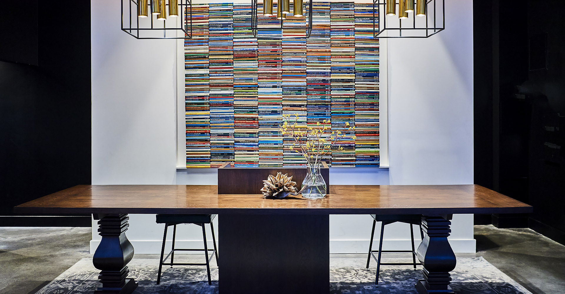 lobby desk in front of an art piece made of multiple stacks of books