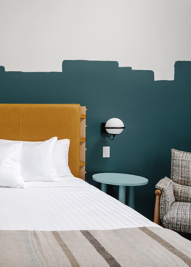 hotel room with teal wall paint and yellow headboard