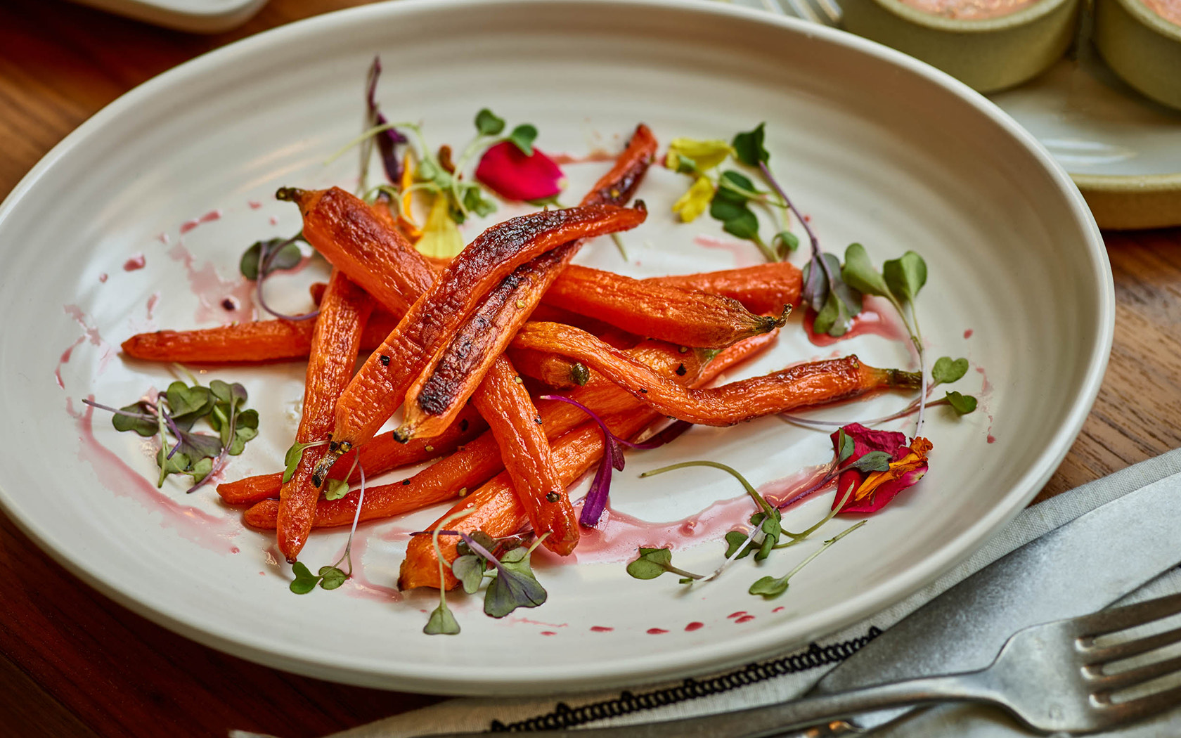 plate with roasted carrots and micro greens