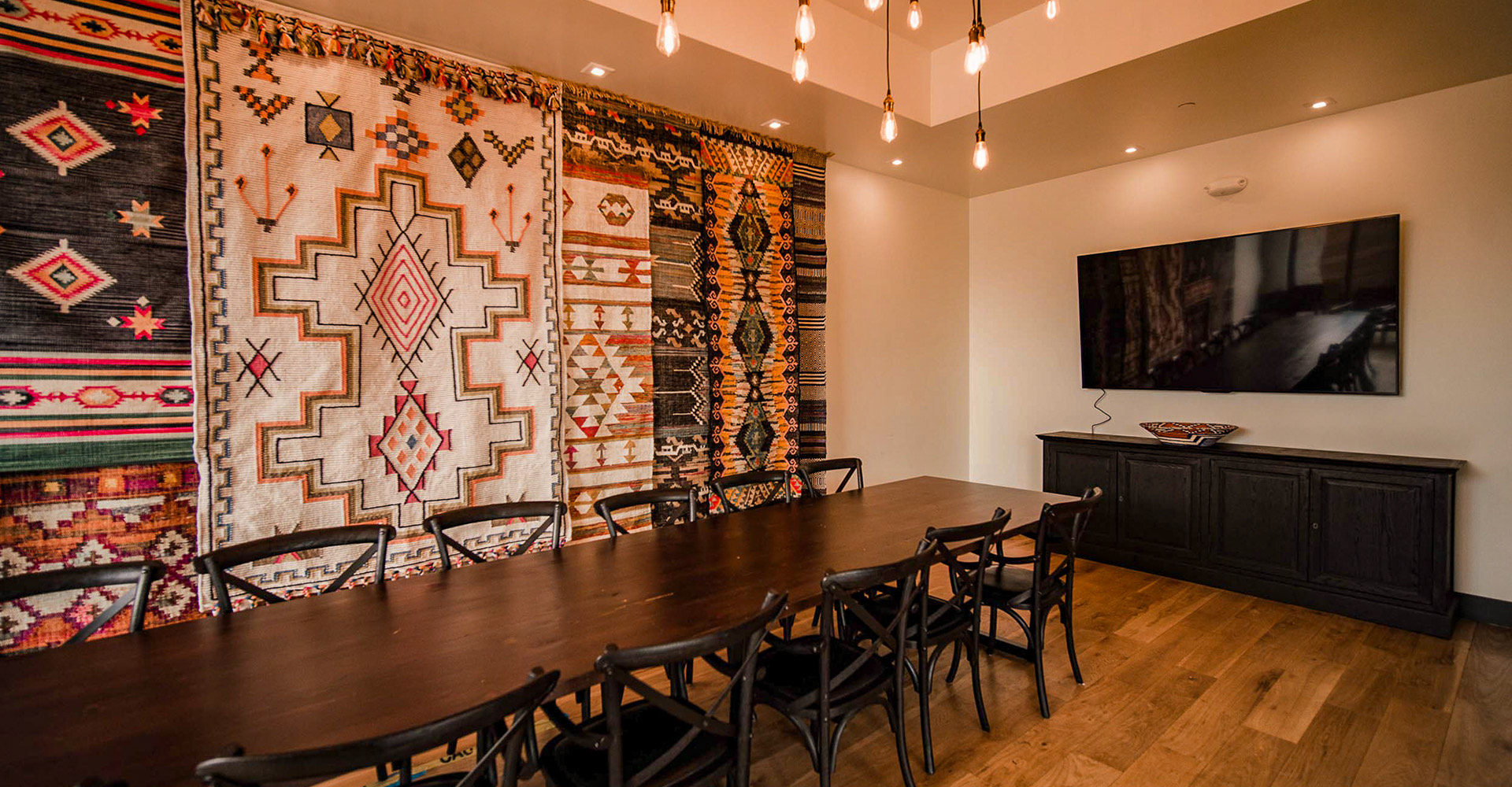 long wooden table in front of a wall with tribal rugs