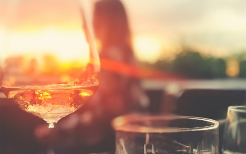 wine glass on a table with the sun gleaming in background