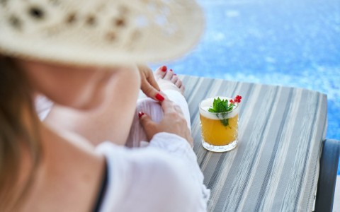 woman sitting on a cushioned lounge chair by the pool with a cocktail