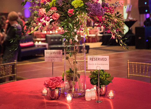 a table set up with a pink table cloth, flowers in vases and signs that say reserved