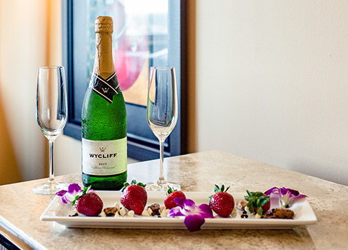 strawberries on a white platter with a champagne bottle and champagne flutes