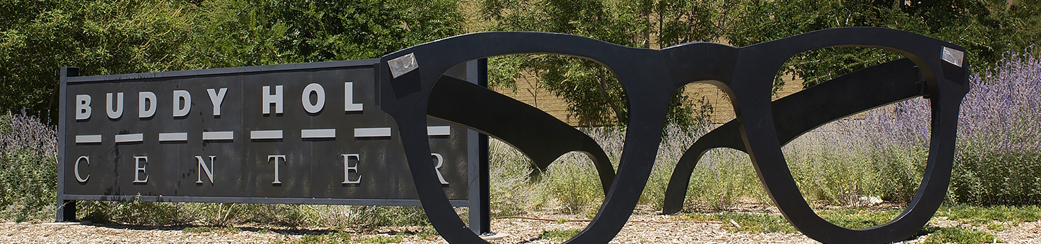 Buddy Holly center sign, blown up statue of black sunglasses next to it