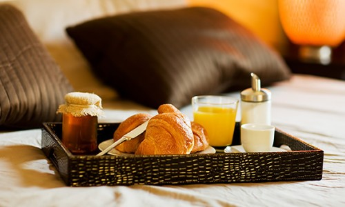breakfast spread of croissants, orange juice, honey and milk on a platter, on a bed