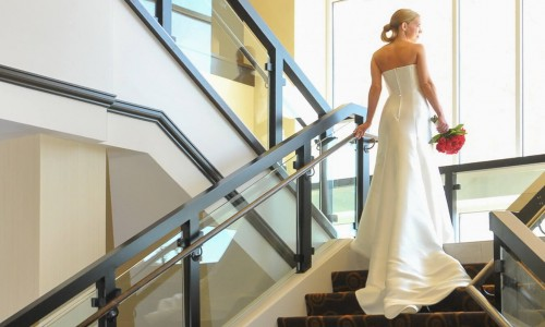 woman in wedding dress walking up set of stairs