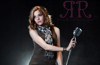 Musician Alyssa Beyers with a standing microphone in hand