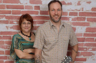 Lance Fry and Rhonda Taylor Musicians posing in front of a red brick wall