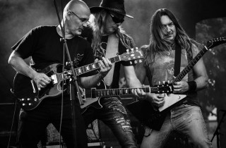 black and white photo of three musicians playing rock guitar