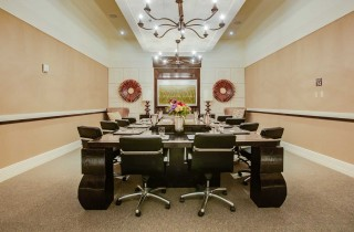 conference room with large tables and chairs and decor hangin on walls